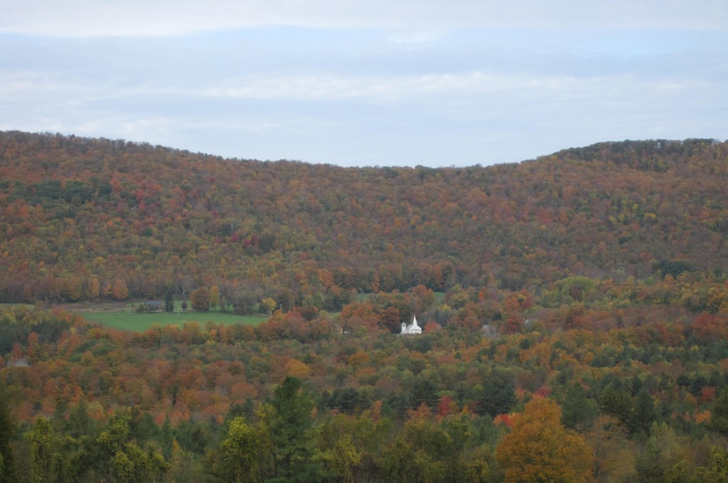 White church in a valley in colorful foliage in vermont